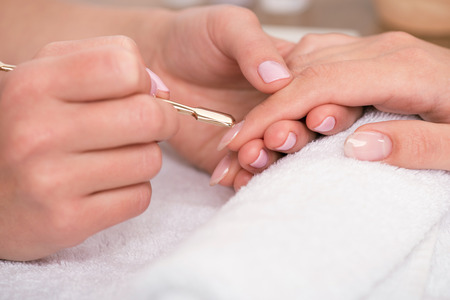 cuticle: client having  manicure by  manicurist cutting cuticle in salon  on white towel close up Stock Photo