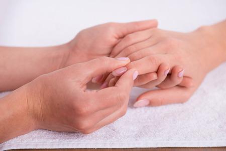 manicurist: client having  hands massage  by  manicurist on white background