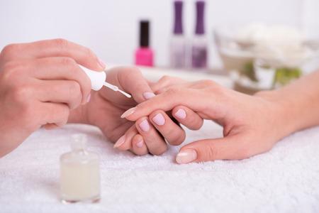 manicure manicure client schilderij nagels met transparante nagellak in salon op witte handdoek te doen Stockfoto