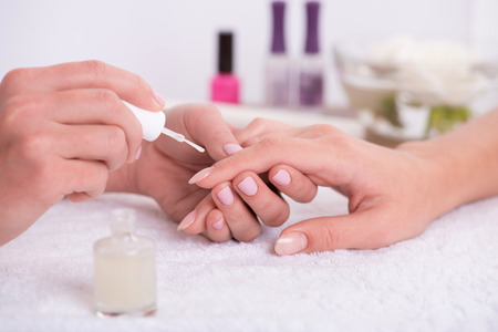 beauty parlor: manicurist doing manicure  client  painting nails with transparent nail polish  in salon  on white towel