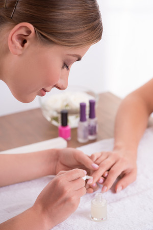 manicurist: manicurist doing manicure  client  painting nails with transparent nail polish  in salon  on white towel