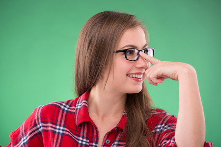 brown haired girl: Portrait of beautiful happy brown haired girl touching her   glasses on green background smiling looking aside Stock Photo