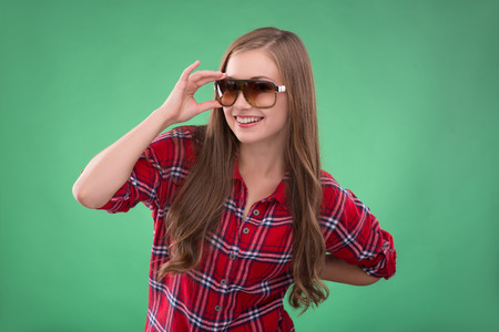 brown haired girl: Portrait of beautiful happy funny  brown haired girl in  glasses on green background smiling looking at camera waist up