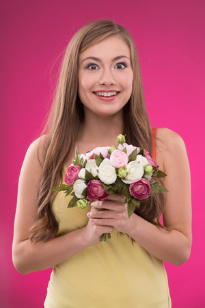 brown haired girl: Portrait of happy beautiful brown haired girl holding  bunch of roses on rose background smiling looking at camera  waist up