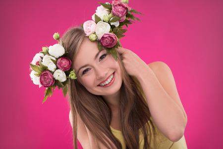 brown haired girl: Portrait of happy beautiful brown haired girl with roses in her hair smiling looking  at  camera on rose background
