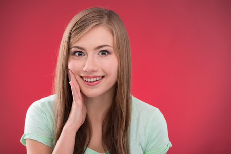 brown haired girl: Portrait of happy beautiful brown haired girl  smiling looking at camera  on red background with copy place