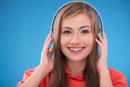 red skinned: Portrait of happy beautiful brown haired girl  with  headphones smiling looking at camera on blue background Stock Photo