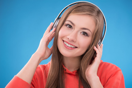 brown haired girl: Portrait of happy beautiful brown haired girl  with  headphones smiling looking at camera on blue background Stock Photo