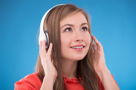 brown haired girl: Portrait of happy beautiful brown haired girl  with  headphones smiling looking aside  on blue background