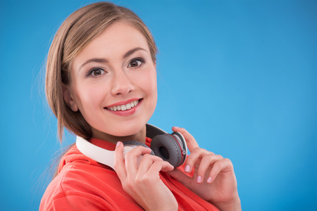 brown haired girl: Portrait of happy beautiful brown haired girl  with  headphones on her neck  smiling looking at camera on blue background  with copy place Stock Photo