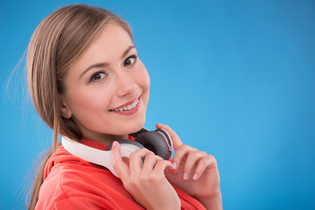 brown haired: Portrait of happy beautiful brown haired girl  with  headphones on her neck  smiling looking at camera on blue background  with copy place Stock Photo