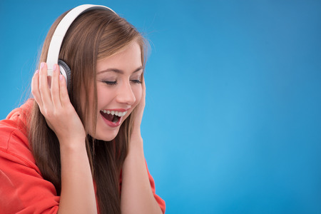 brown haired girl: Portrait of happy beautiful brown haired girl  with  headphones smiling looking aside  on blue background  with copy place