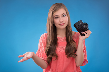 brown haired girl: Portrait of happy beautiful brown haired girl  with photo camera looking at camera on blue background  with copy place waist up