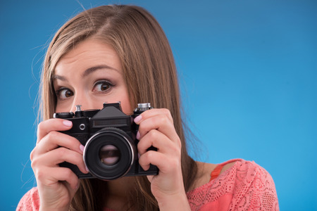 brown haired girl: Portrait of happy beautiful brown haired girl looking out  photo camera on blue background  with copy place looking at camera Stock Photo