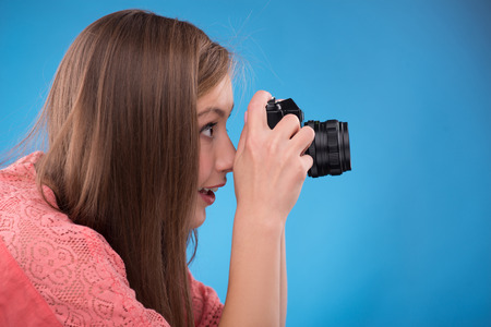 brown haired girl: Portrait of happy beautiful brown haired girl  with photo camera on blue background  with copy place side view Stock Photo