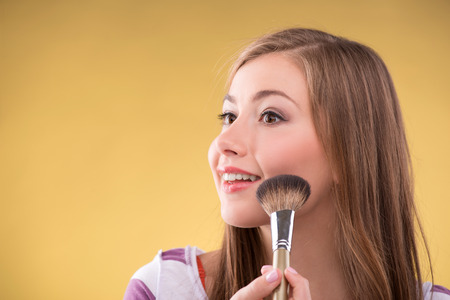 brown haired girl: Portrait of happy beautiful brown haired girl doing make up with brush for rouge looking aside with copy place close up