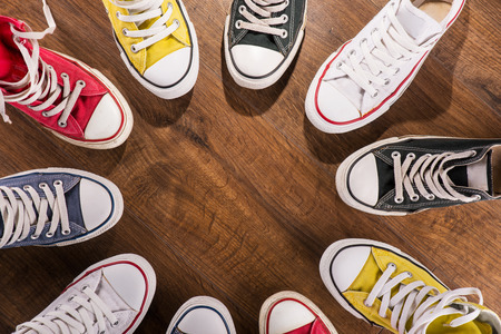 sport kids: cool youth white yellow red blue black  gym shoes standing in circle  on brown parquet  wooden floor with copy place  top view Stock Photo