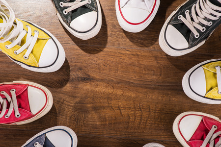 youth background: cool youth white yellow red blue black  gym shoes standing in circle  on brown parquet  wooden floor with copy place  top view Stock Photo