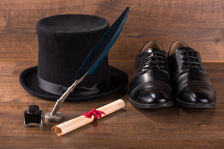 black classic  hat near refined  black patent leather shoes  and bundle and ink and black feather on brown parquet  wooden floor Stock Photo