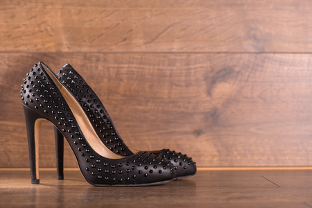 high  heeled: black classic  high heeled refined  black patent leather shoes  on brown parquet  wooden floor with copy place