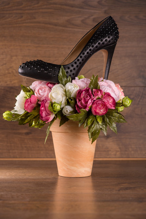 patent leather: black classic  patent leather shoes  on bunch of roses on  brown parquet  wooden floor Stock Photo