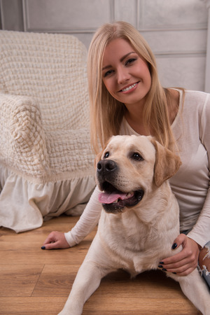knitted jacket: Beautiful  slender blond girl in jeans and beige knitted jacket  sitting on floor  with Labrador Retriever smiling looking at camera