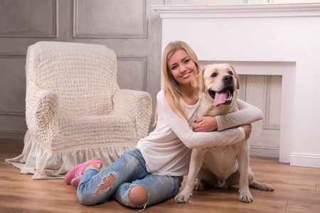 knitted jacket: Beautiful  slender blond girl in jeans and beige knitted jacket  sitting on floor  embracing  Labrador Retriever smiling looking at camera full length