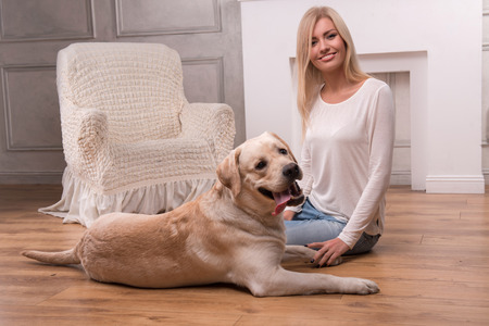 knitted jacket: Beautiful  slender blond girl in jeans and beige knitted jacket  sitting on floor  with Labrador Retriever smiling looking at camera full length
