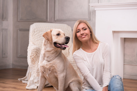knitted jacket: Beautiful  slender blond girl in jeans and beige knitted jacket  sitting on floor  with Labrador Retriever smiling looking at camera waist up