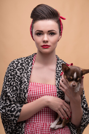 red skinned: Portrait of pretty brunette  girl in rose dress and red headband and cloak  in retro style  with Chihuahua looking at camera waist up