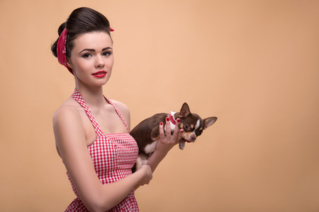 red skinned: Portrait of pretty brunette  girl in rose dress and red headband   in retro style  with Chihuahua looking at camera waist up with copy place