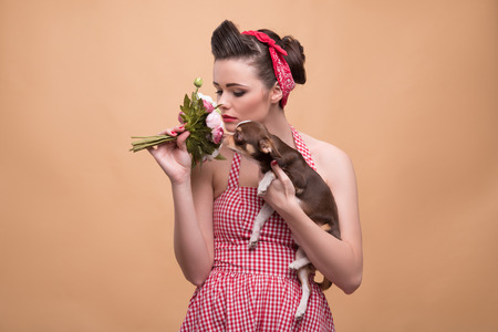 red skinned: Portrait of pretty brunette  girl in rose dress and red headband in retro style  with Chihuahua and bunch of roses waist up