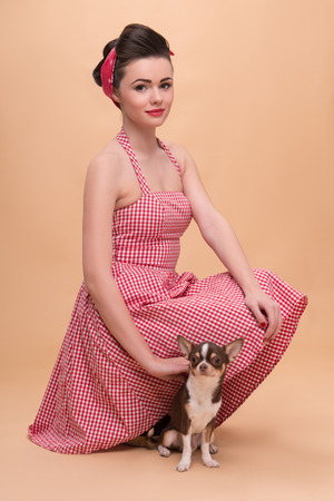 Portrait of pretty brunette girl in rose dress and red headband in retro style with Chihuahua looking at camera full length