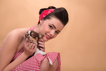 red skinned: Portrait of pretty brunette  girl in rose dress and red headband in retro style  with Chihuahua on knees looking at camera  close up with copy place Stock Photo