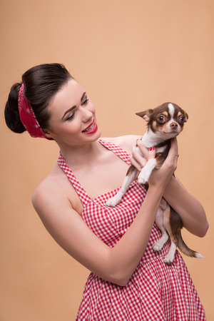 waist up: Portrait of pretty brunette  girl in rose dress and red headband   in retro style  with Chihuahua smiling waist up