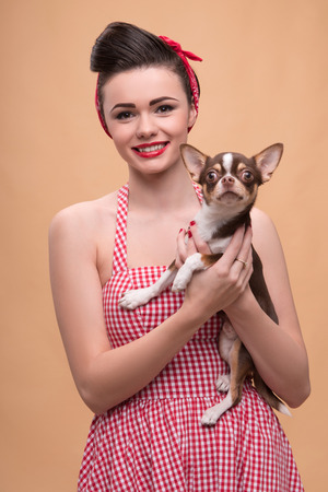 waist up: Portrait of pretty brunette  girl in rose dress and red headband   in retro style  with Chihuahua smiling looking at camera waist up