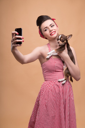 red skinned: Portrait of pretty brunette  girl in rose dress and red headband in retro style  with Chihuahua doing selfie smiling looking at phone  waist up