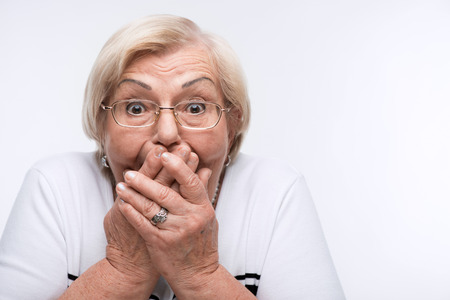 Elderly woman closes her mouth, ears and eyes with hands Stockfoto