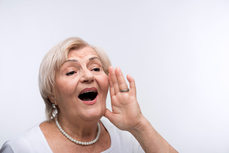 bad temper: Elderly lady shouting putting hands by her mouth Stock Photo