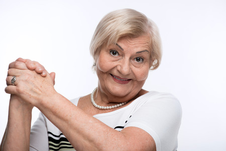 clasping: Happy elderly woman clasping hands Stock Photo