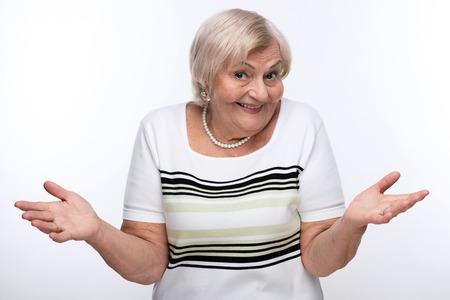 hesitating: Closeup of elderly woman shrugging shoulders