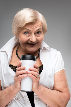 residental care: Elderly woman holding thermos cup Stock Photo
