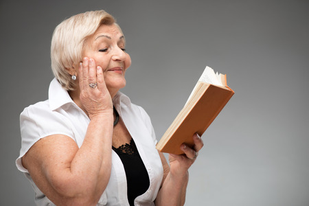 residental care: Elderly woman holding yellow book