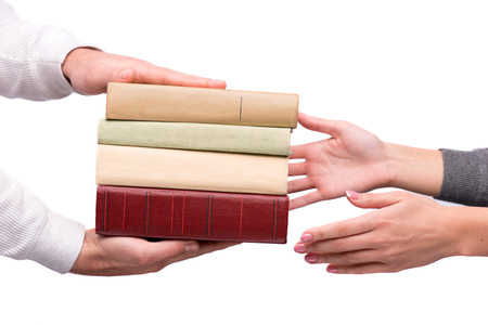 Hands passing heap of books photo