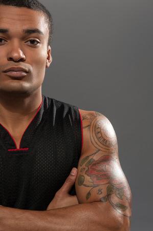 mani incrociate: Giovane giocatore di basket africano bello con le mani incrociate