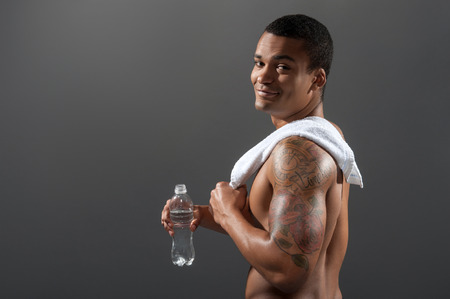 man drinking water: Young Africana sportsman drinking water after workout