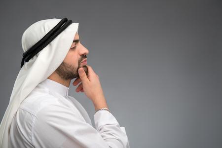 hombre arabe: Hombre �rabe pensando duro con la mano en la cara Foto de archivo