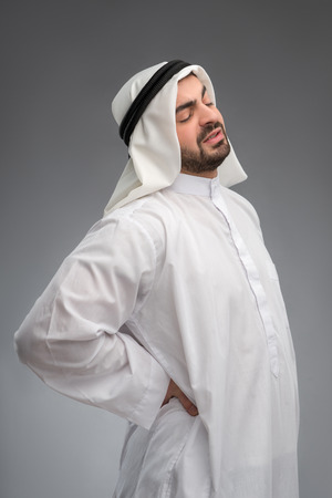 Middle aged Arab touching his aching waist photo