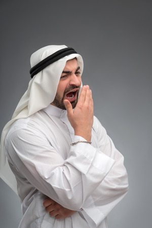 Arab man raising his hands being tired photo