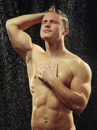 nude wet: Handsome young man taking a shower Stock Photo